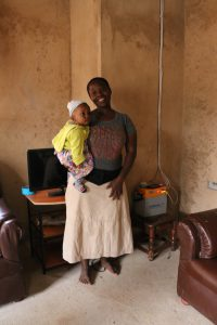 A. Kagaruki and her daughter in front of the TV and solar battery. Image by Carmen Rosa