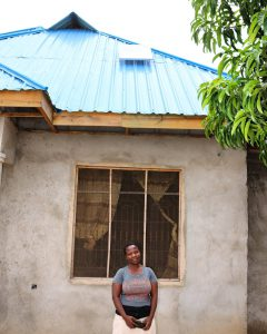 A. Kagaruki in front of her house with SHS. Image by Carmen Rosa