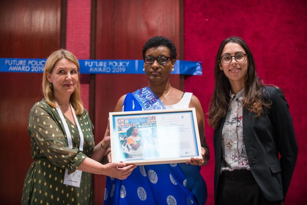 Vorstandssprecherin Alexandra Wandel gemeinsam mit Moderatorin und Vertreterin von Ruanda auf der Bühne, wie sie stolz die Preisurkunde von Ruanda präsentieren.