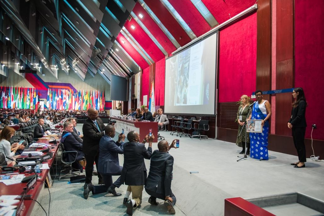 Der Future Policy Award: Preisverleihung für Gold Gewinner Ruanda. Ruanda's Vertreterin steht auf der Bühne und nimmt ihre Urkunde entgegen.