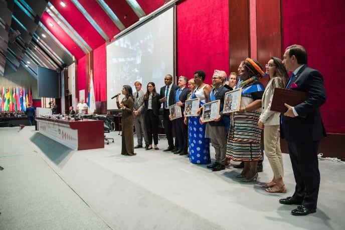 Preisträgerinnen und Preisträger zeigen ihre Urkunden. Im Vordergrund steht Kekashan Basu mit einem Mikrophon.