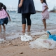 Garbage on the beach with family playing water in the sea on background, environmental pollution of tropical sea